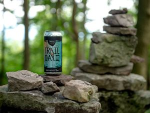 A beer can labeled Trail Day sits on top of a low rock wall in a forest. Trail Day is a partnership between TNC and Troegs Brewing to support the Kittatinny Ridge.