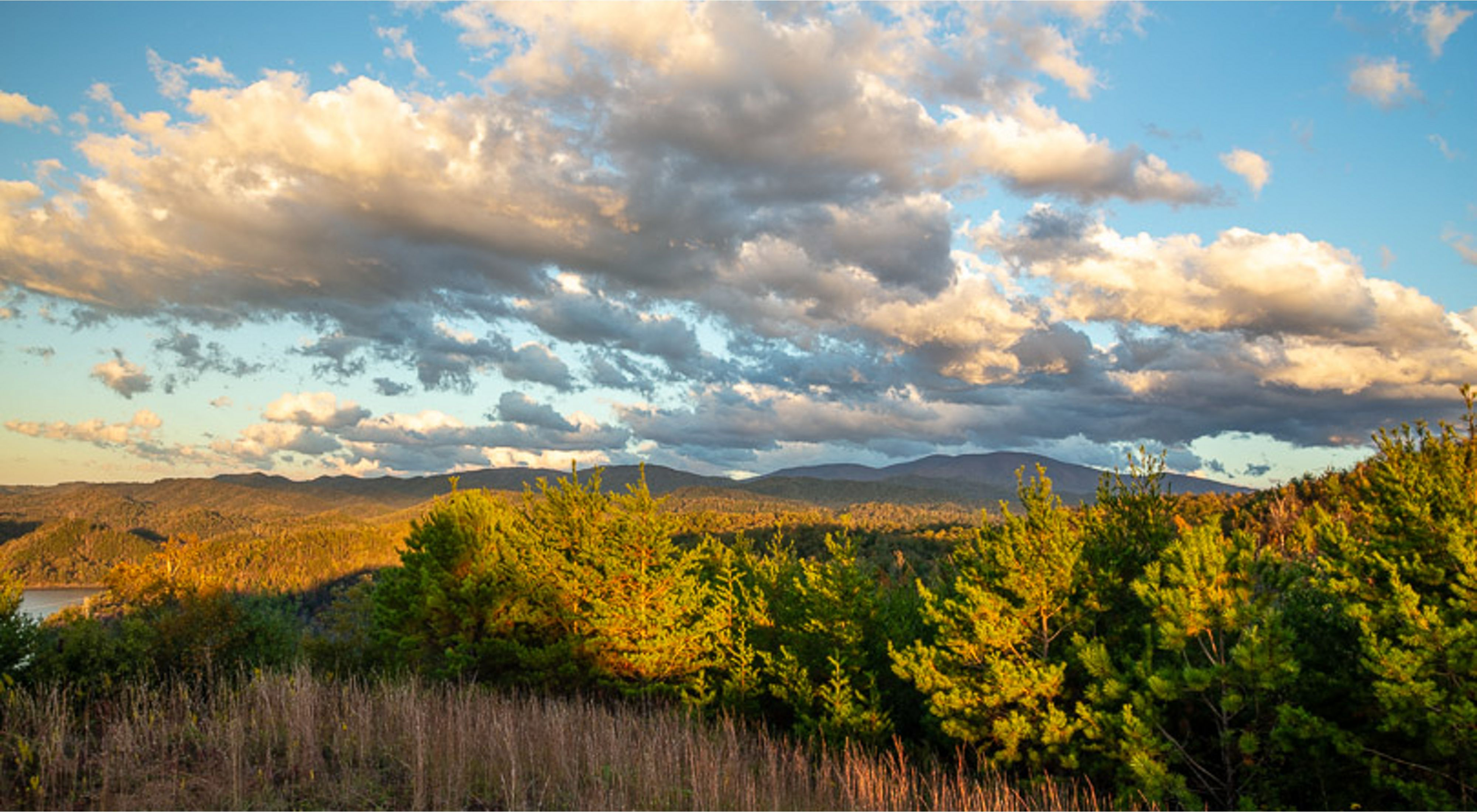 Clouds hover over a sunny mountain valley.