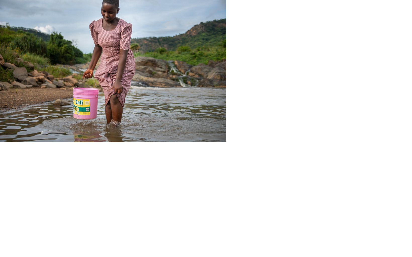girl collecting water in a bucket