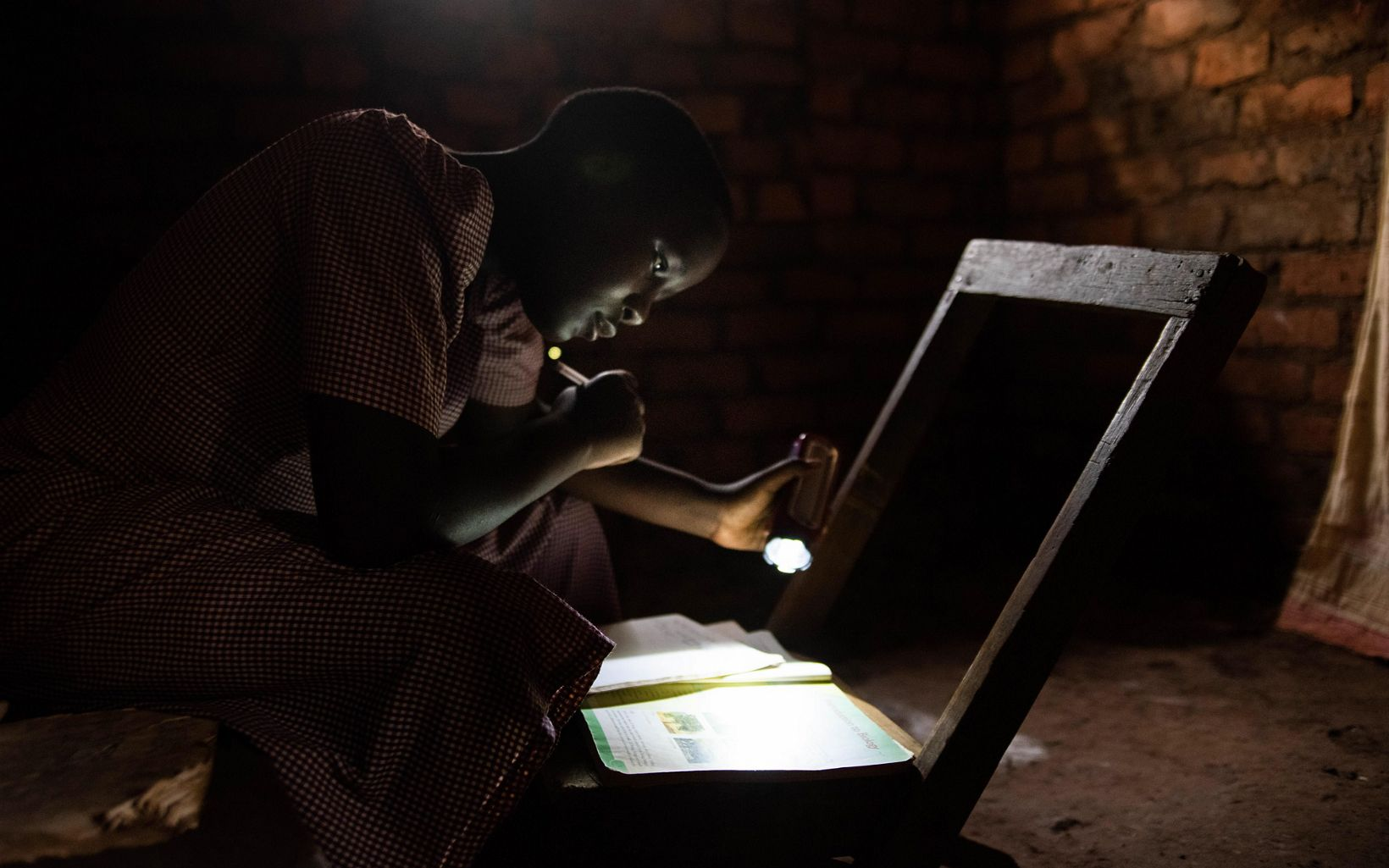 girl reading with a flashlight