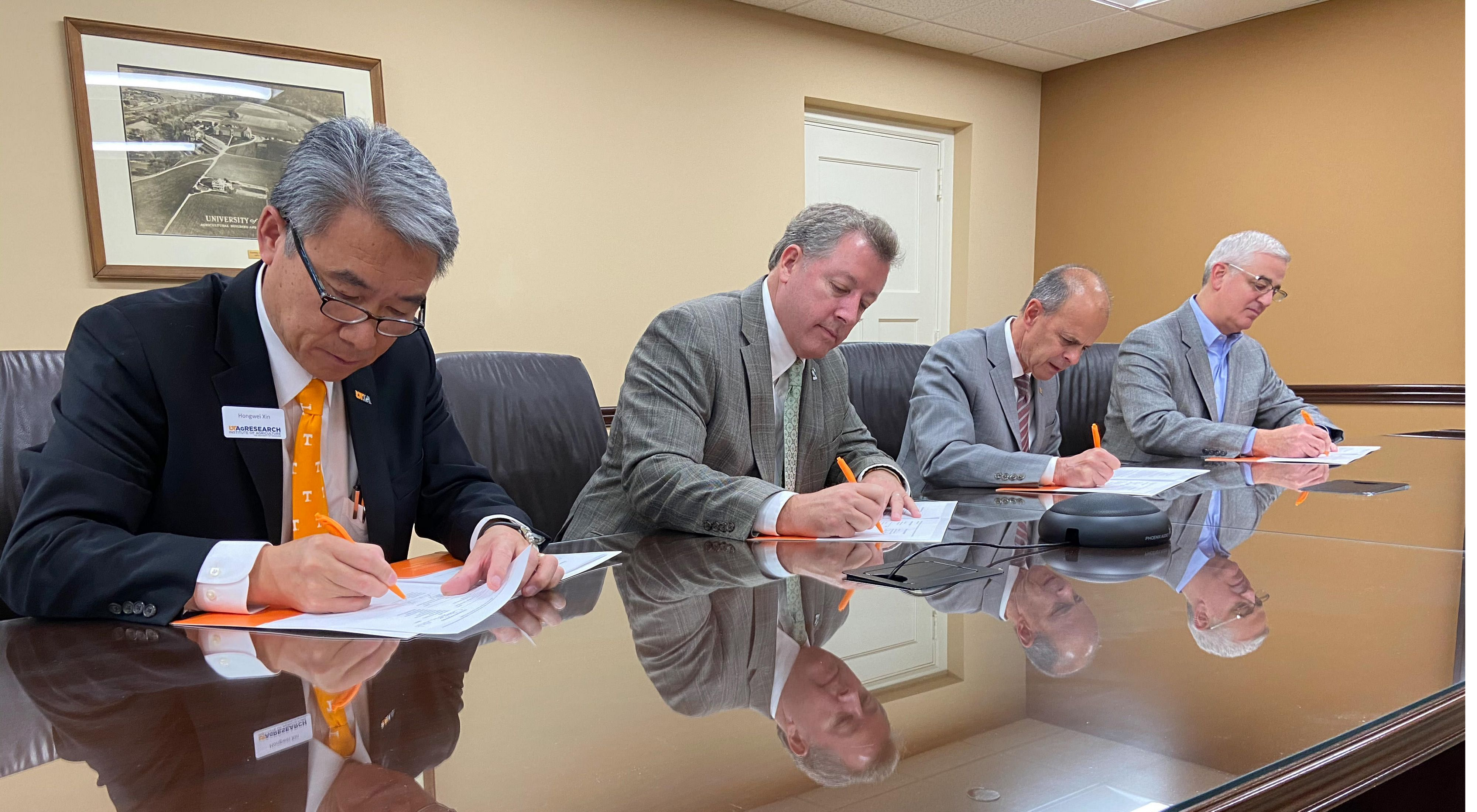 Three men sit at a table and sign papers.