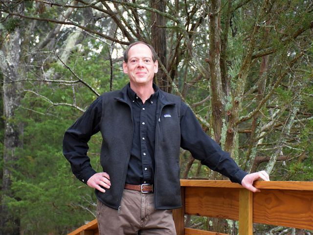 Candid portrait of VA Deputy State Director Bill Kittrell. A smiling man poses outdoor next to a wooden railing with tall trees in the background.