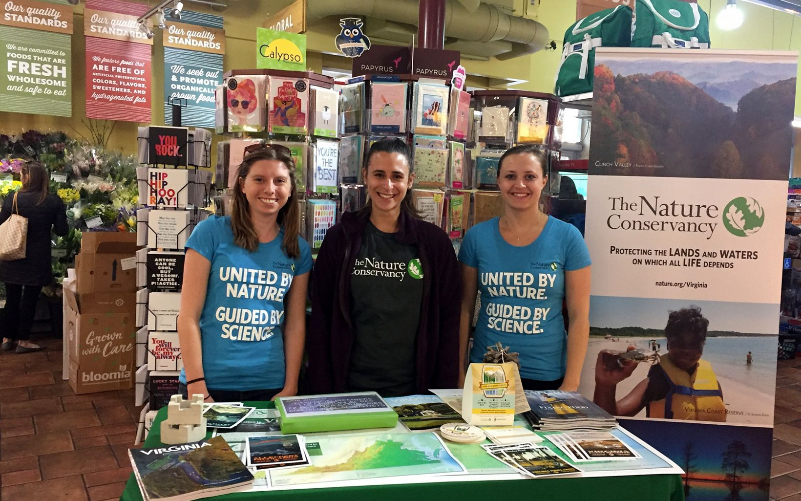 The Nature Conservancy staff tables at a WFM 5% Day event.