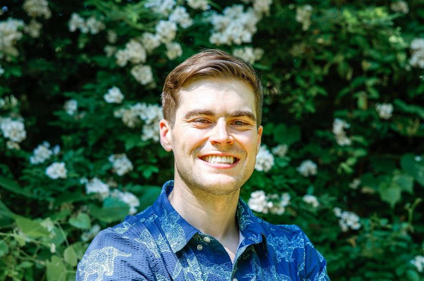 Candid headshot of Government Relations Association Zachary Sheldon. A smiling man poses in front of a tall green bush with small white flowers. He is wearing a blue shirt with a triceratops design.
