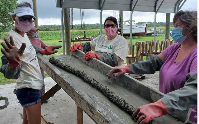 Three women stand around an elevated table using a concrete mixture to create a long, thin piece of oyster reef substrate.