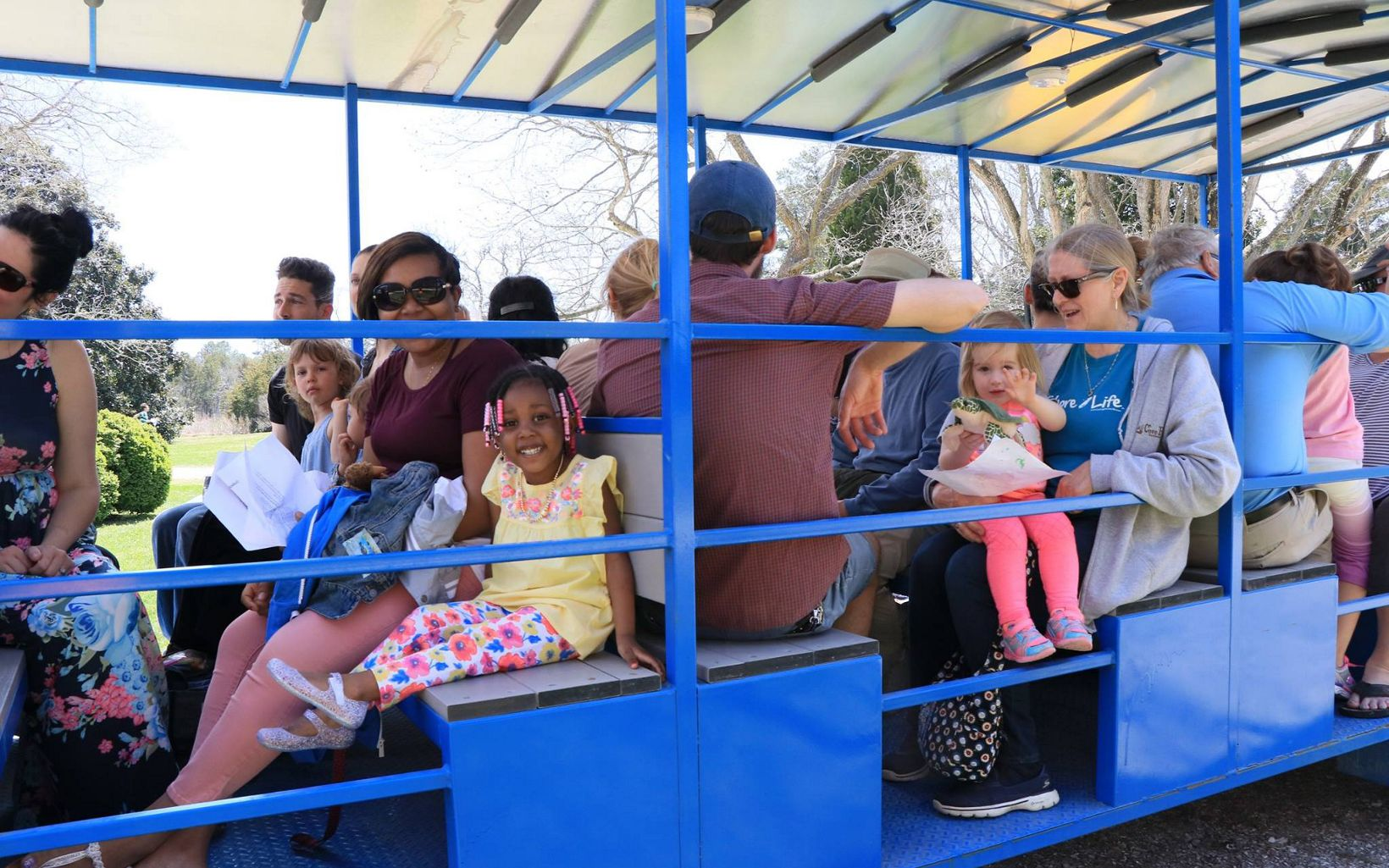 Families seated in a large open sided wagon for a tour of Brownsville Preserve.
