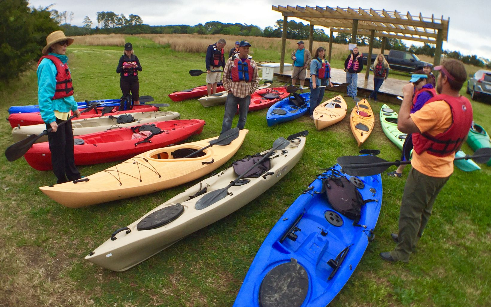 A group of about 10 people stand around two rows of colorful kayaks.