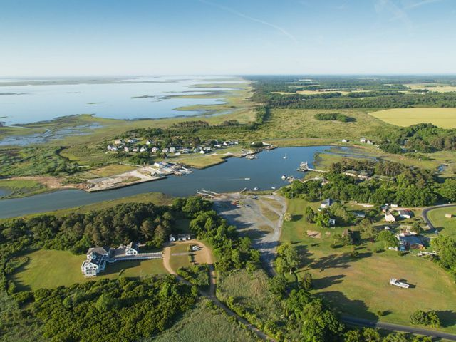 Aerial view of the town of Oyster, Virginia. Houses surrounded by trees and open fields cluster around a wide inlet.