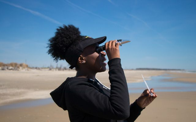 A girl holds a monocular to her eye while conducting science experiments on a beach.