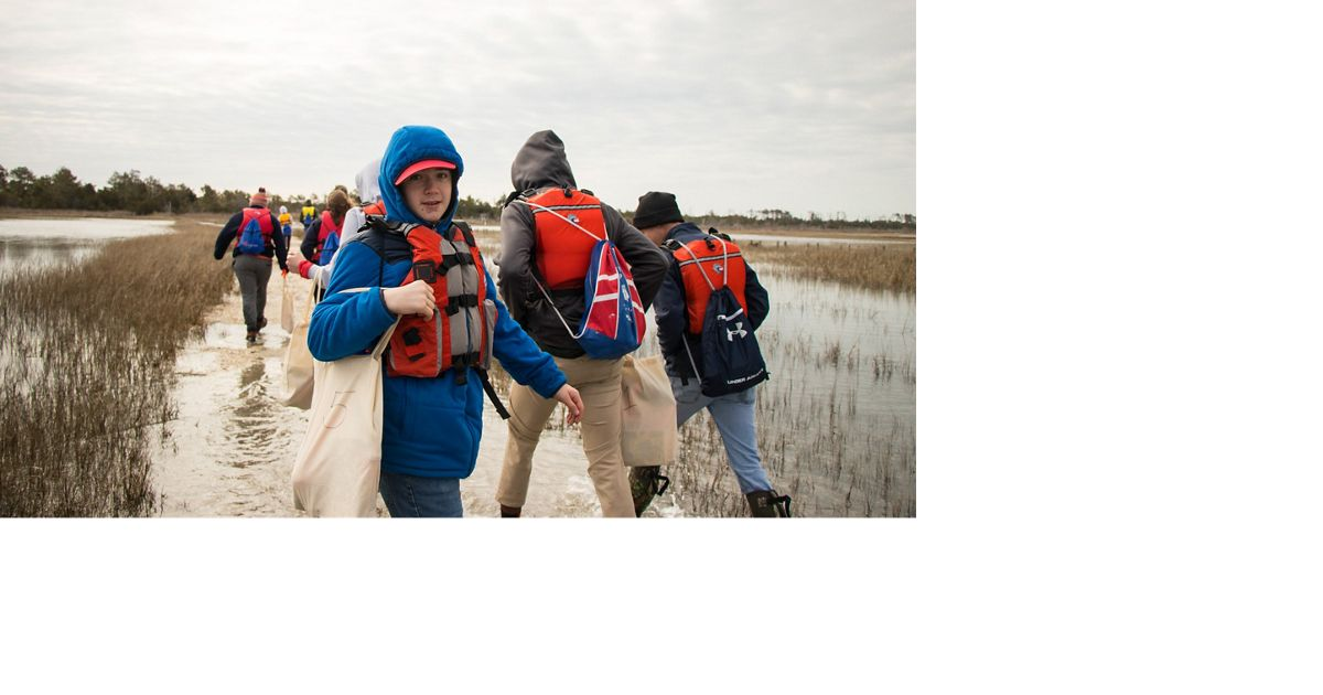 Raymond Agar with classmates from Broadwater Academy trek through the marsh on Parramore Island.