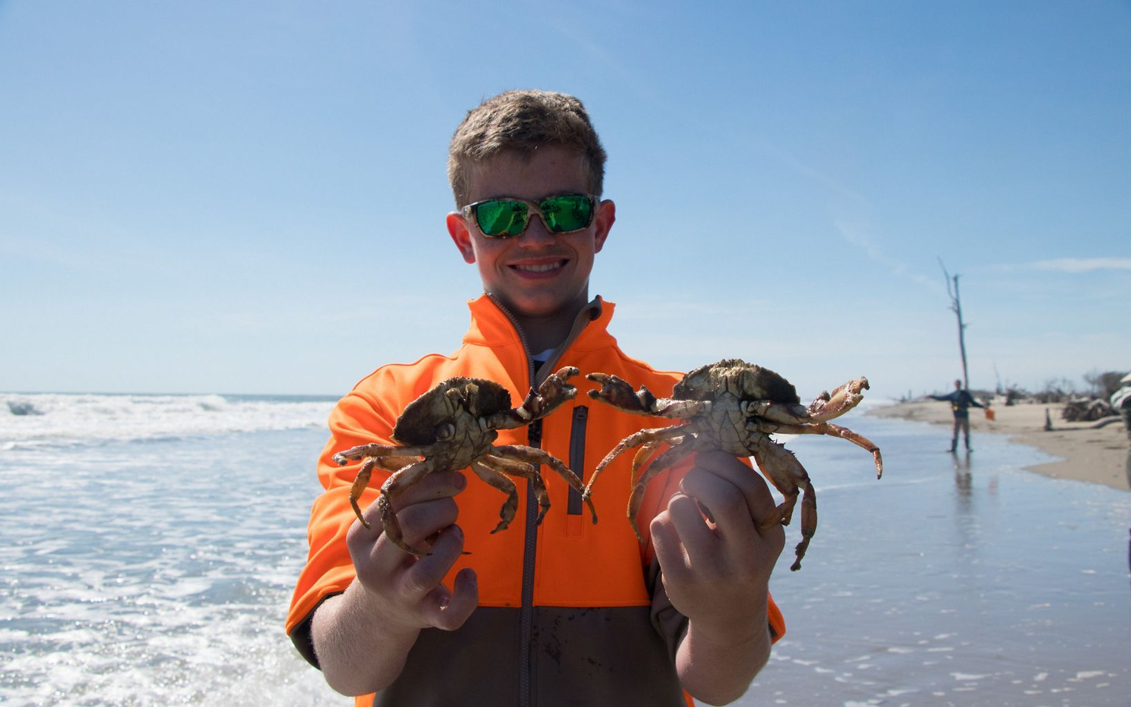 A smiling boy holds up two crabs.