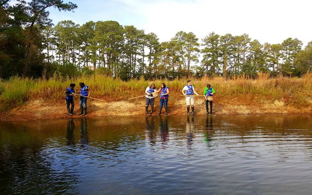 Six children standing in groups of two use dip nets to explore a tidal creek.