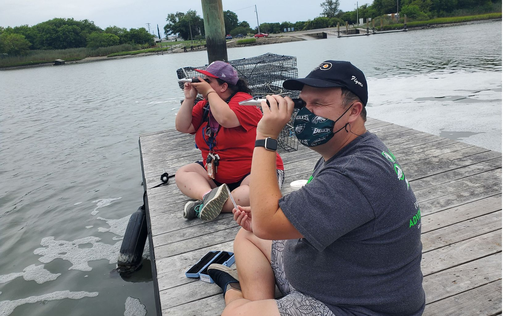 Two people sit on a dock looking through monoculars