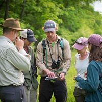 Vermont staff and partners gather around a map at Helen W. Buckner Memorial Natural Area at Bald Mountain.
