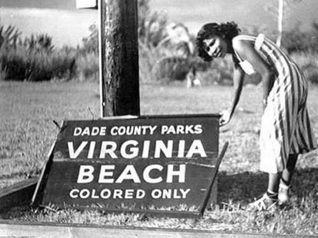 """Historical photo of a visitor standing on Virginia Key Beach standing next to a """"colored only"""" sign."""