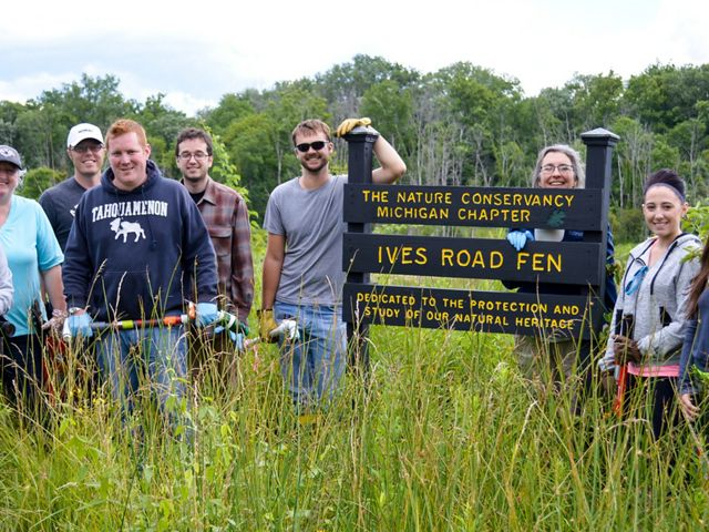 A group of smiling people with tools pose next to the Ives Road Fen Preserve sign.