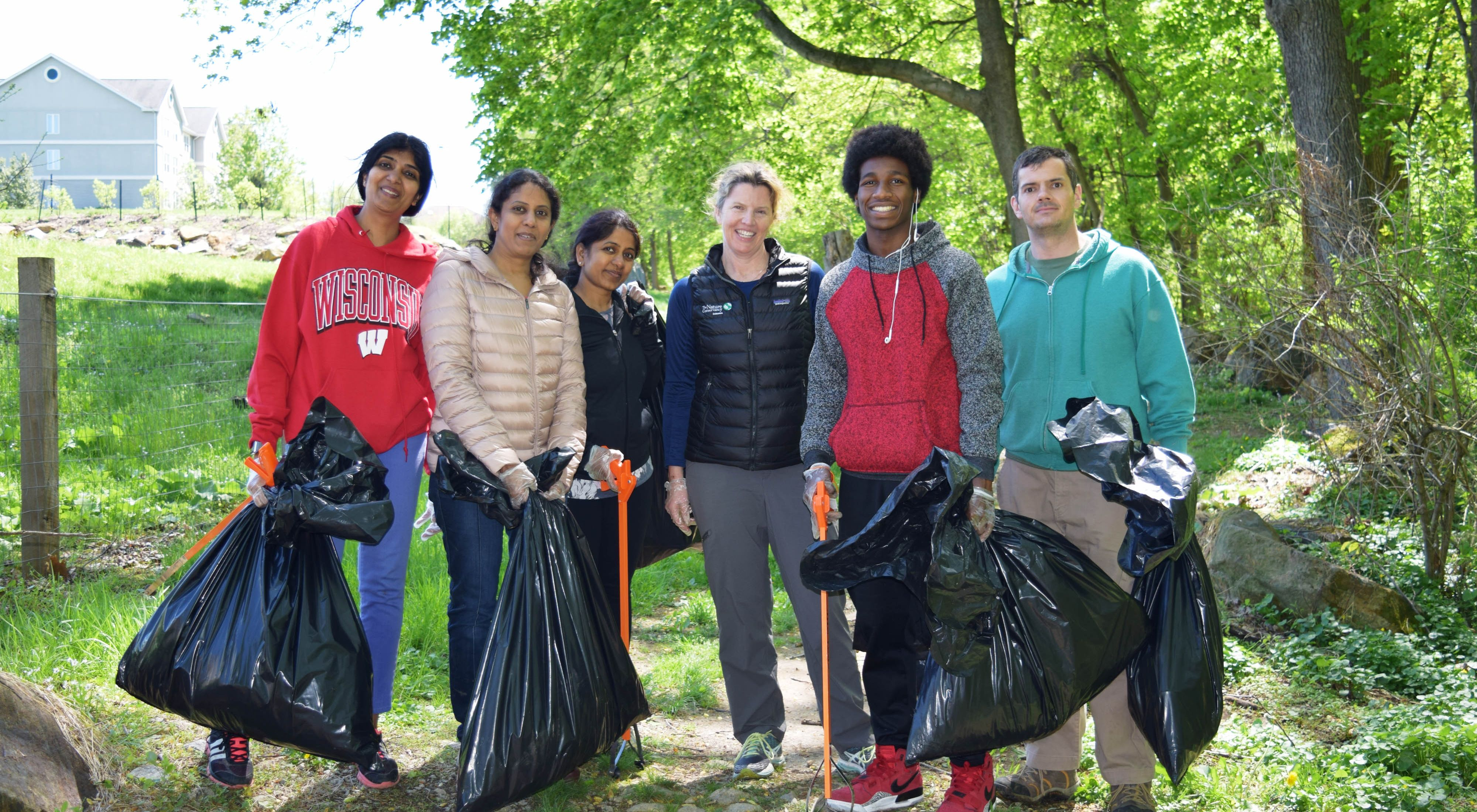 Six people pose together during a stream cleanup event. They are holding large black plastic trash bags and carrying long orange grabbers.