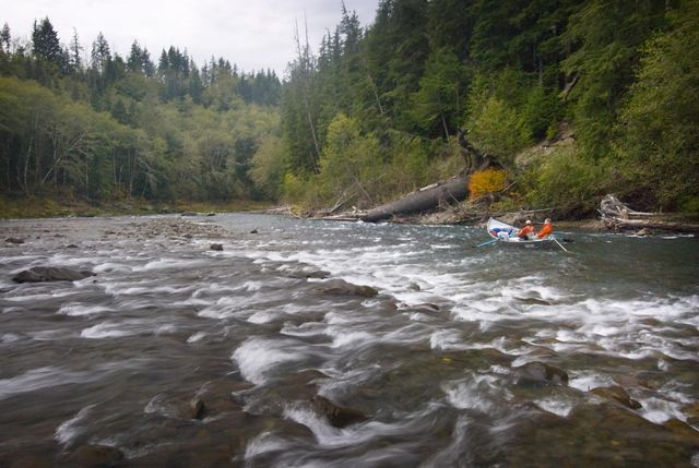 Two people ride a dory down the Hoh River in Washington state.