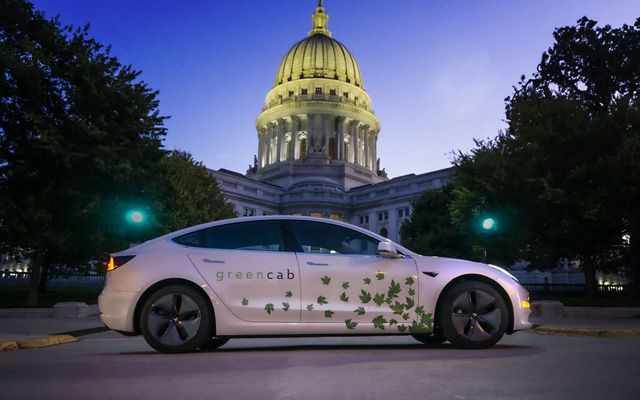 Green energy car parked in front of Wisconsin state capitol building.