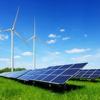 Solar panel and wind turbines on green grass with blue sky background.