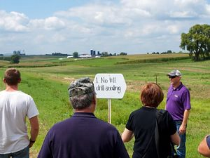"Farmers meet in a field by a sign that says ""1. No till drill seeding""."
