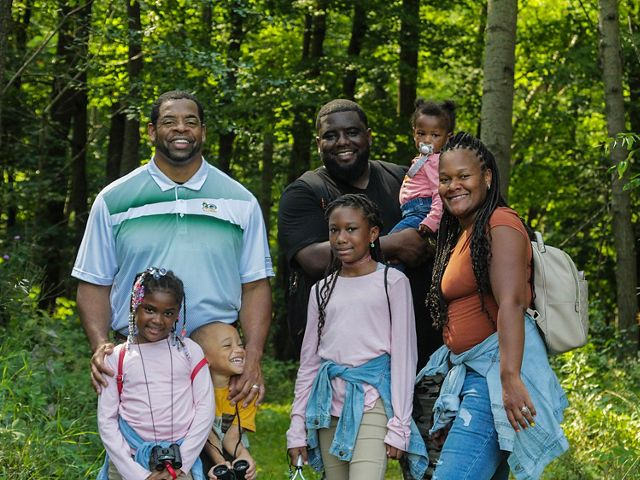 Older man in polo shirt with Green Bay Packers logo with young woman wearing a backpack, young man carrying a child in his arms and three young children standing in of them with forest in background.