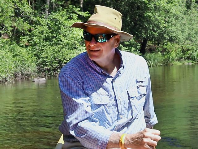 Man in blue-checked shirt, sunhat and sunglasses paddles canoe on a river with forest in the background.