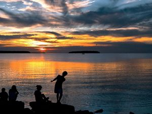 Orange sunset reflected in waters of a bay with silhouettes of people including children on shore.