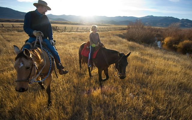 Two ranchers on horseback near sunset on an Idaho ranch.