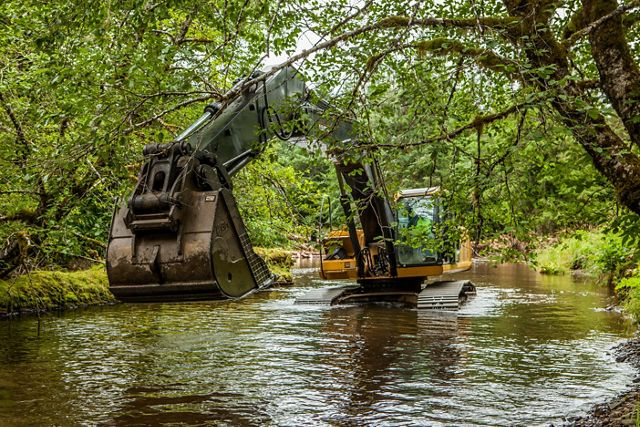 Photo of a front end loader in a river adding woody debris.