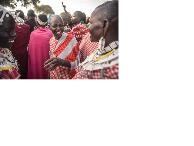Maasai women watching Maasai men performing traditional dance and chanting during a circumcision ceremony in Tanzania. The Nature Conservancy is working to protect the land that the Hadza people of Tanzania depend upon to maintain their hunter gatherer way of life.