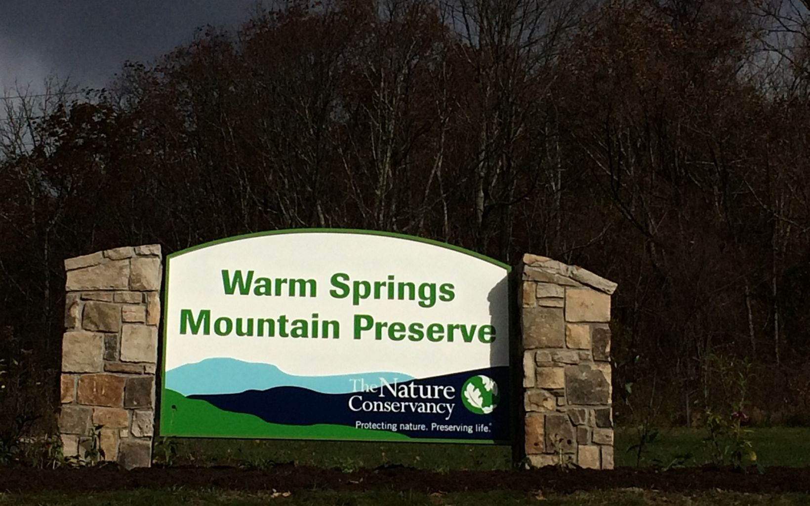 A large sign held up by two stone pillars welcomes visitors to Warm Springs Mountain Preserve.
