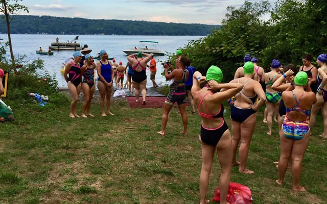 A group of about 20 swimmers pose variously on the lawn of a swimming dock area. Many have green swim caps on. All are wearing one-piece swimsuits.