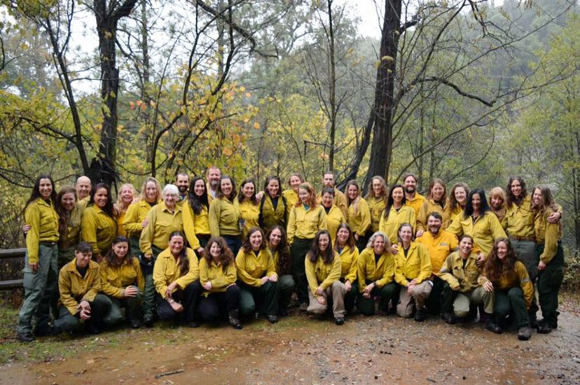 Group photo of several dozen women taking during a fire training exchange. The women are wearing yellow fire gear and posing in a clearing in a forest.