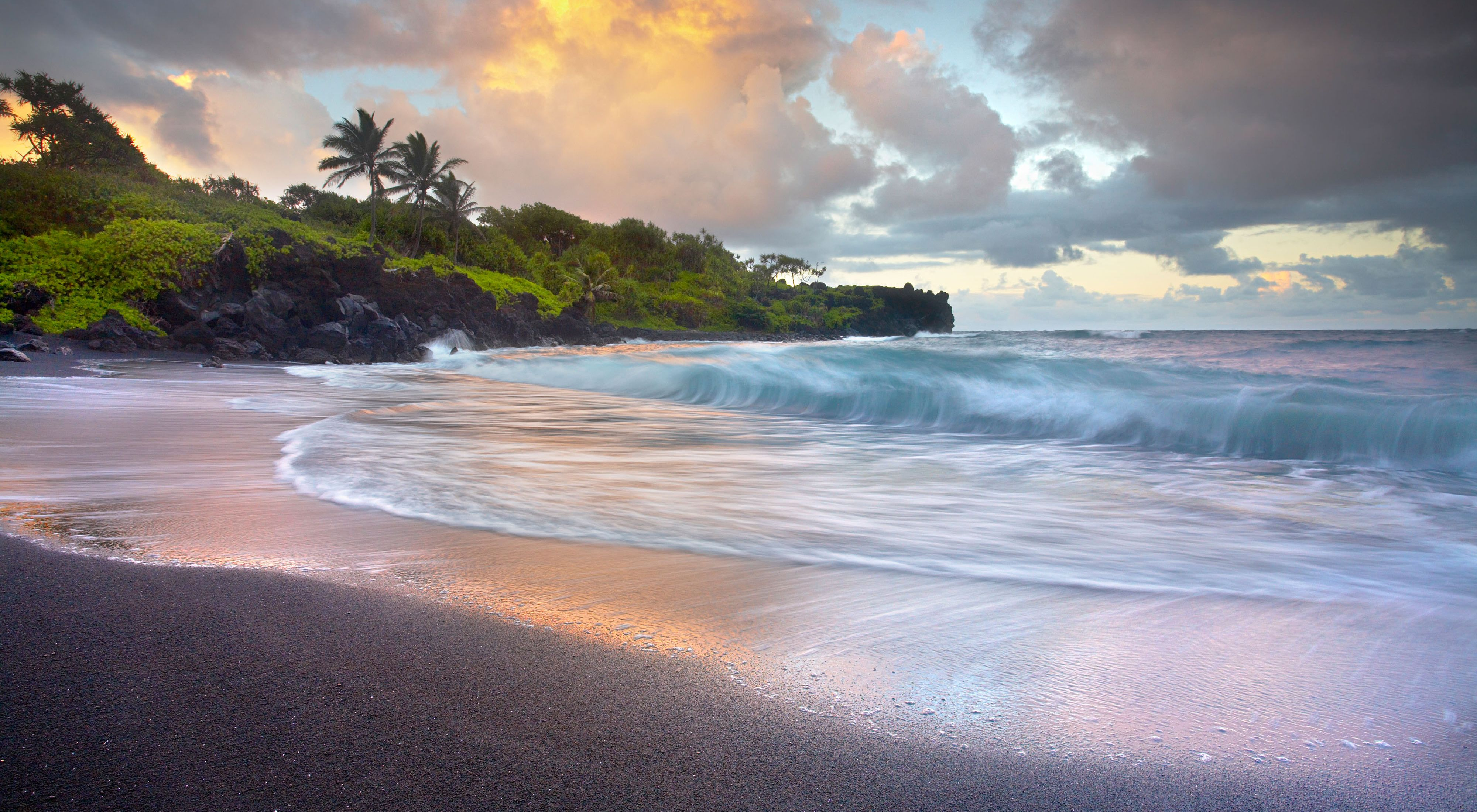 Waves crash on the black sand beach of Waianapanapa Sands with a rocky outcrop topped with lush greenery in the distance.
