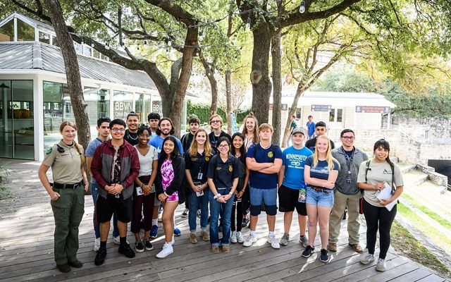 A group of 20 young participants of Austin's Park Ranger Cadets pose for a photo in a park.