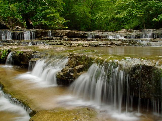 A water fall flows over big brown rocks.