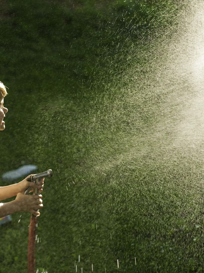 Young boy spraying garden hose.