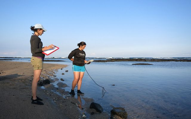 Two researchers stand on a beach with clipboards and a water monitoring instrument.
