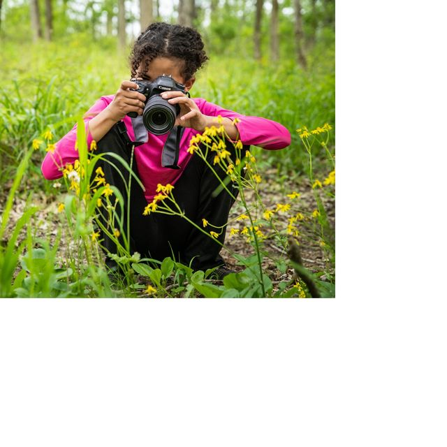 A sitting girl takes a picture of wildflowers.