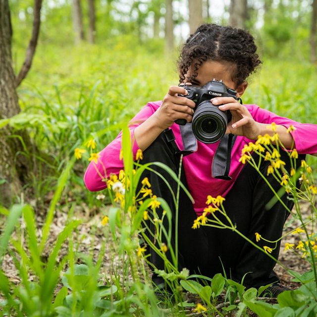 A girl photographs wildflowers.