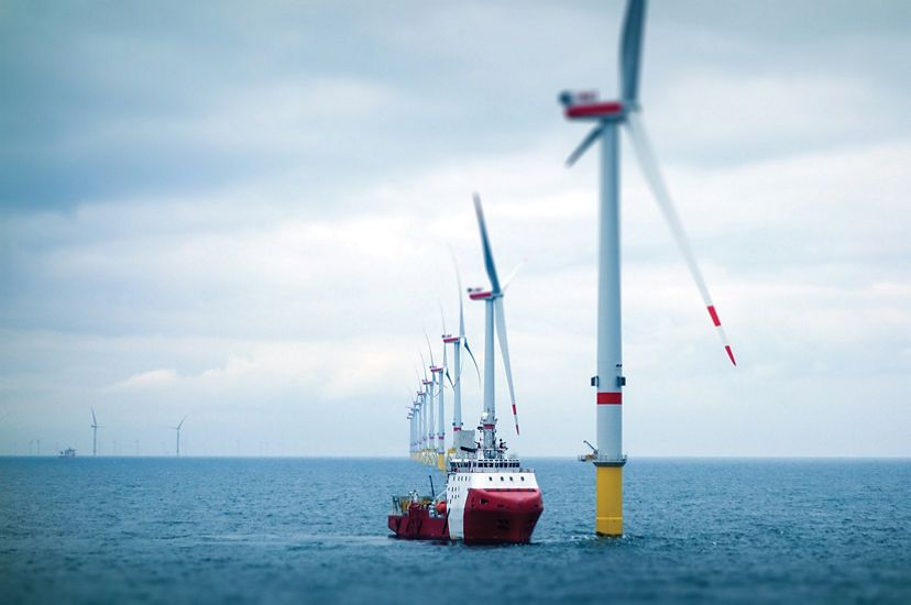 Wind farm towers with transfer vessel in the ocean.