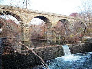 A waterfall flows under an historic stone bridge.