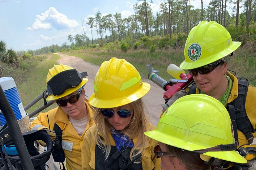 Photo of four women in fire gear looking at a map for a controlled burn.