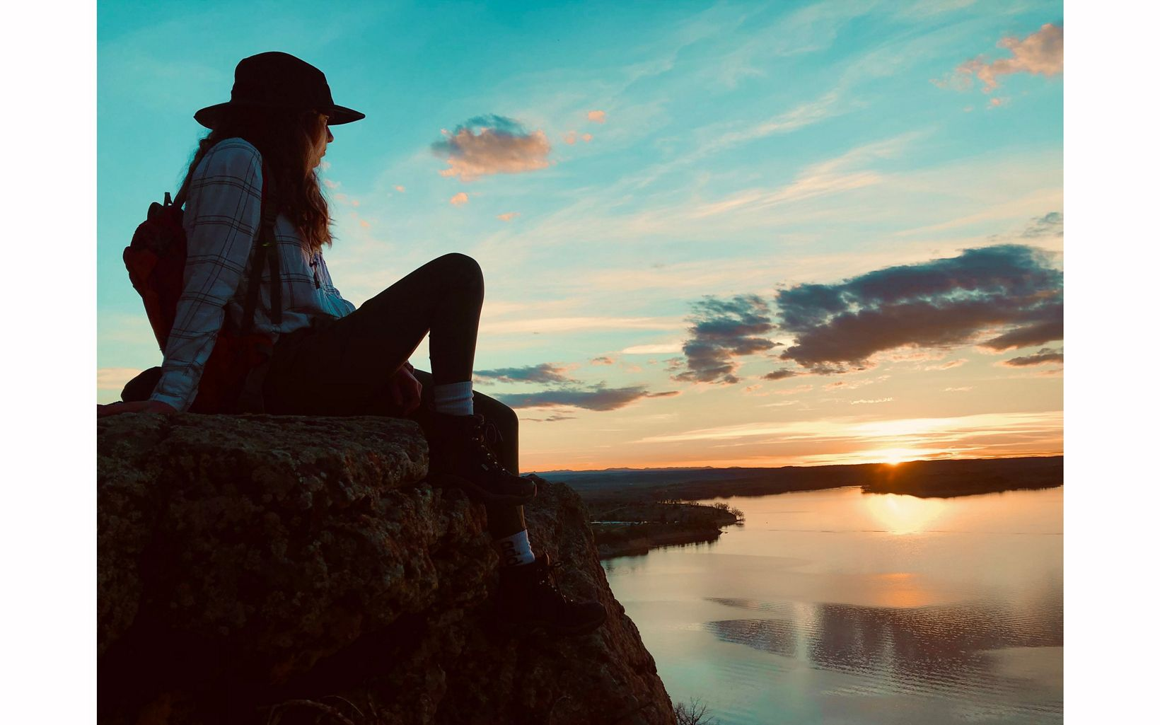 Person sits on rock next to water at sunset.