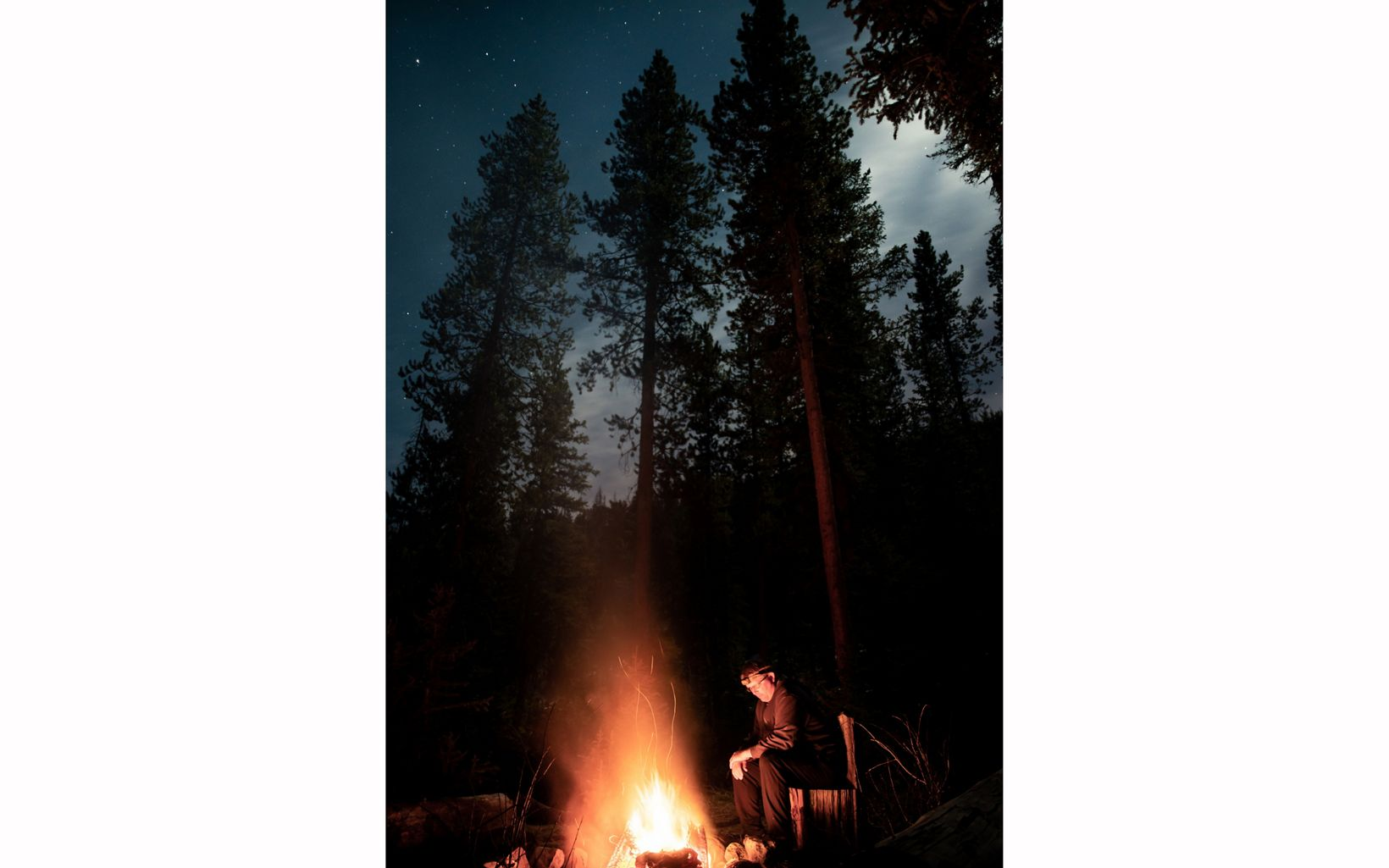 Man by campfire in forest at night.
