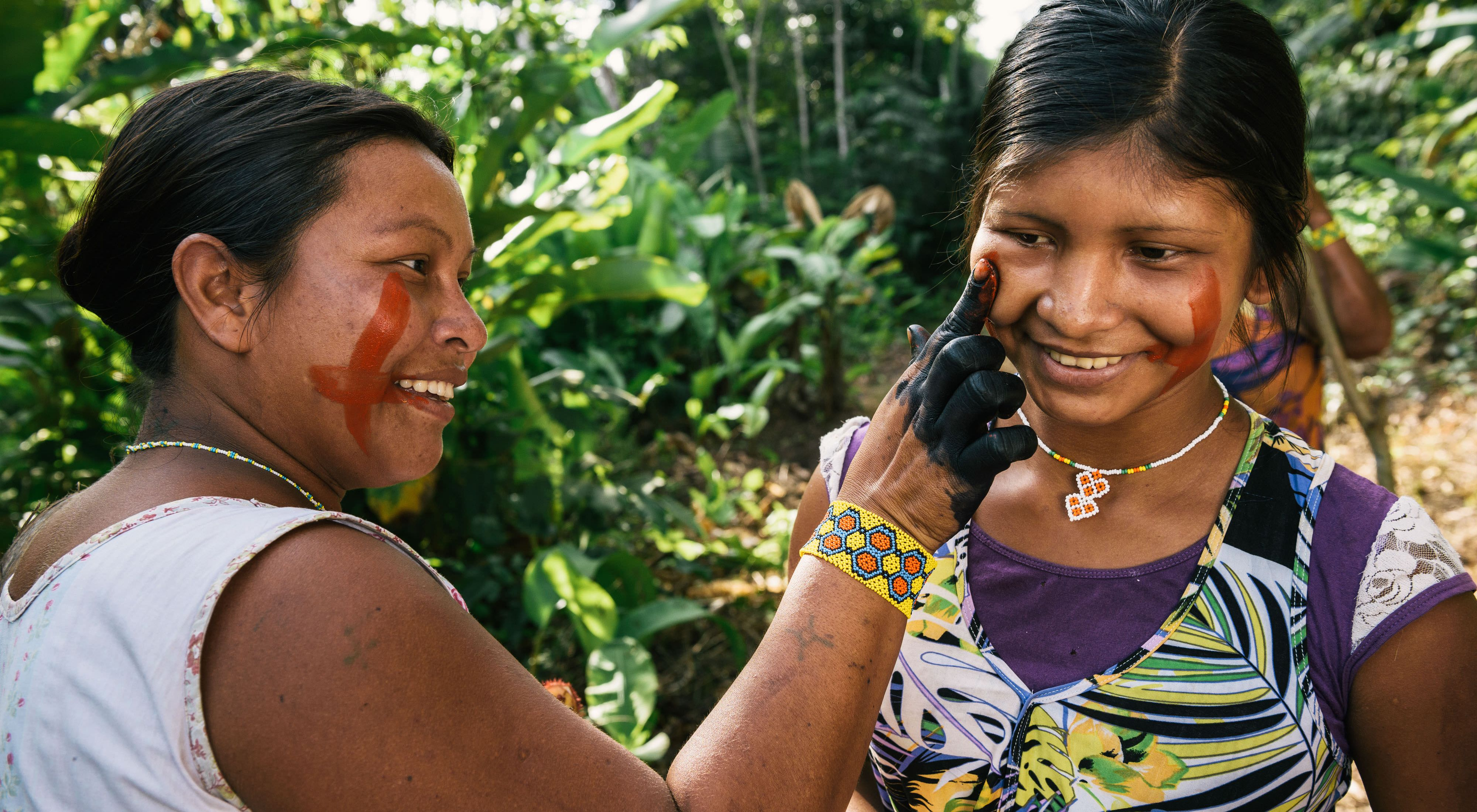 Xikrin women painting each other's faces in a forest near the Pot-Kro Village, Brazil.