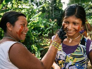 Xikrin women painting each other's faces.