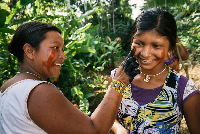 Xikrin women paint each other's faces with red paint