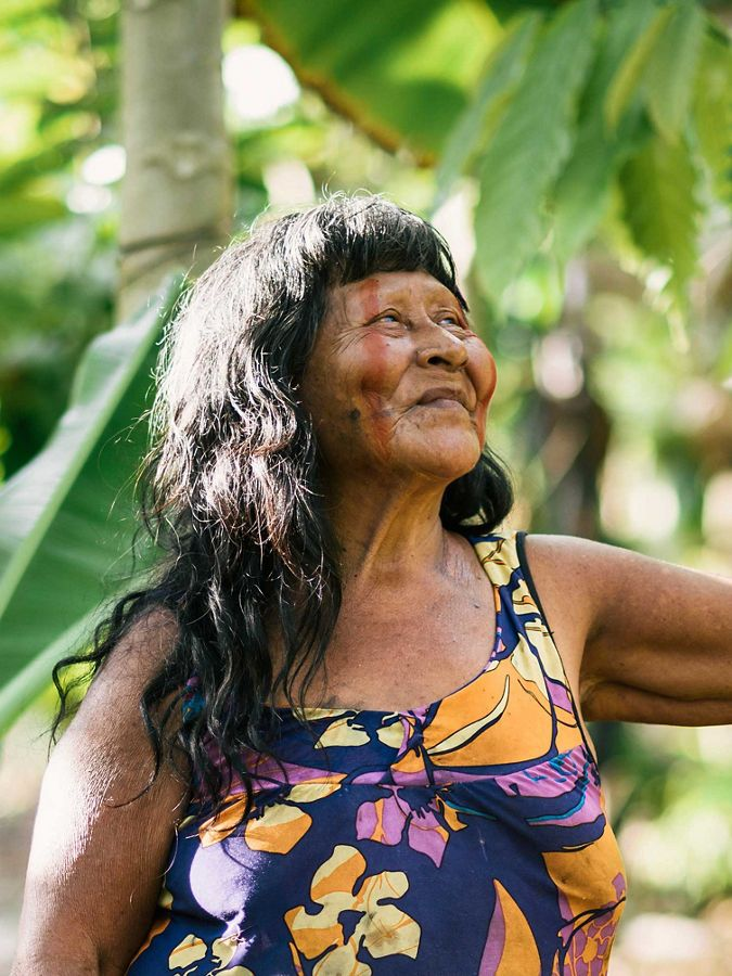 Woman leaning against a tree holding a machete.